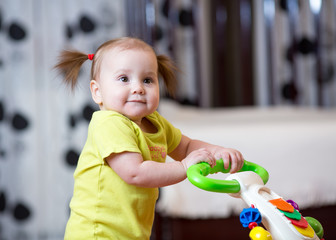 First steps of little child girl in baby walker