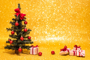 Little Christmas tree with some decoration ball and xmas gifts in small boxes on golden shining bokeh background, image with copy space
