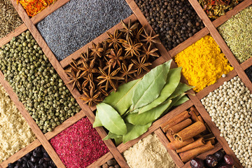 Fototapete - Bright herbs and spices in wooden trays on shop window. Set seasonings for cooking, in  box with cells.
