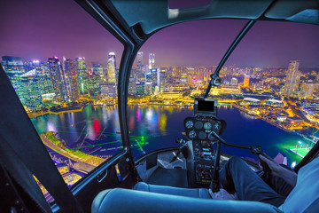 Tuinposter Aziatische Plekken Scenic helicopter flight above Singapore skyline at dawn. Night urban aerial scene. cockpit interior with financial district skyscrapers at night on Singapore harbor.