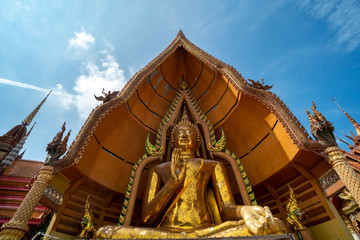 Big golden Buddha in Wat Tham Suea,Kanchanaburi. The thai temple in rice field.