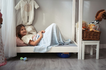 Girl child plays in small bed with toys, in real