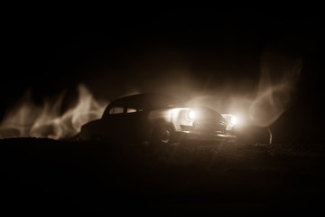 Silhouette of old vintage car in dark foggy toned background with glowing lights in low light.