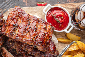 Delicious barbecued ribs on an rustic wooden chopping board with potato wedges and sauce, glass of drink with ice, top view