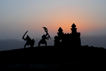Medieval battle scene on sunset. Silhouettes of fighting warriors on sunset background. Wall mural