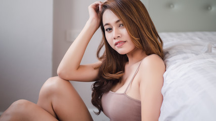 Happy beautiful asian woman in sleepwear at home in the morning bedroom..