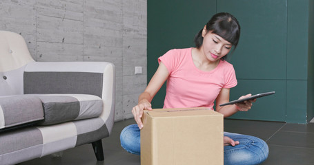 Woman doing online shop with clothes , packing and checking on tablet with parcel