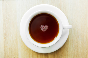 White cup of black tea with bubbles in a shape of heart. White cup on wooden table