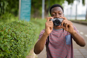 Young handsome African man taking pictures with camera in park