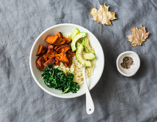Sweet potato, couscous, spinach, avocado buddha bowl on grey background, top view. Vegetarian comfort food concept