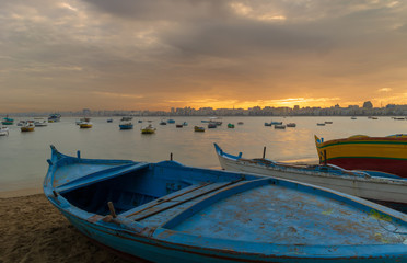 Fishing boats on the beach at dusk with Alexandria skyline in far distance and colorful sky at sunrise, Egypt