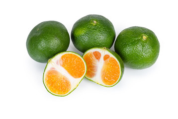 Whole ripe green tangerines and one tangerine cut in half