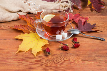 Tea on rustic wooden table with autumn leaves and scarf