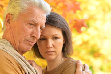 Portrait of sad woman and senior man hugging