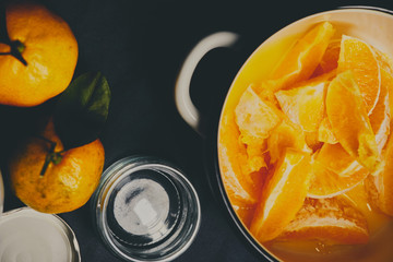 Peeled oranges in white pot ready to be cooked for jam