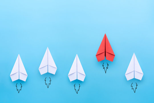 Red paper plane leading among a white planes on blue background. Business competition and Leadership concept