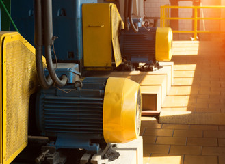 Two large electric motors in the production workshop, against the background of sunlight, electric motor