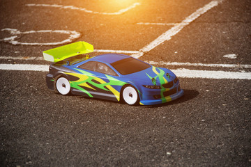 Automotive sport on the radio, multi-colored radio-controlled car stands on the asphalt road, close-up, model