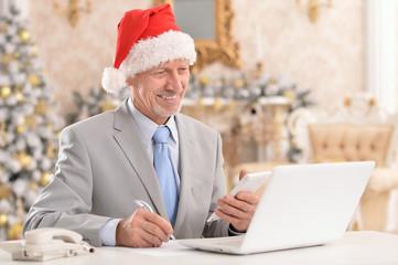 Portrait of senior man working with laptop