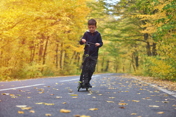 Cute boy riding scooter, outdoor in autumn environment on sunset warm light