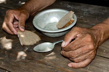 Hands the poor old man's, piece of bread and empty bowl on wood background. The concept of hunger or poverty. Selective focus. Poverty in retirement.Homeless. Alms Fototapete