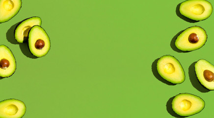 Wall Mural - Fresh avocado pattern on a green background flat lay