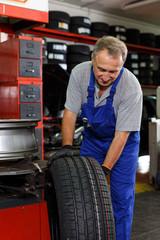 Mechanic replacing tyre on car wheel