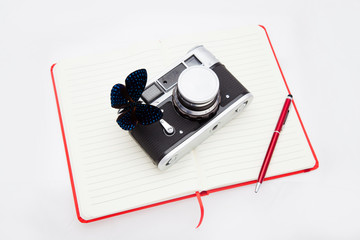 A blue morpho butterfly and a camera lie on an open notebook and a ballpoint pen lies next to it. Explore butterflies, ethnology.