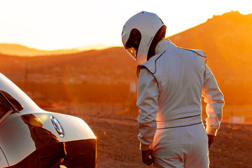 Fotobehang F1 A Helmet Wearing Race Car Driver In The Early Morning Sun Looking At His Car Before Starting