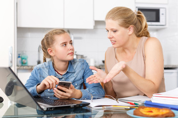 Mother scolds her daughter for playing  smartphone