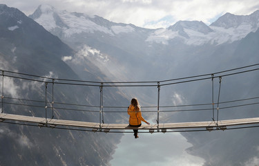 A woman sits on a swing bridge beyond Schlegeis reservoir on a sunny autumn day near the alpine village of Ginzling