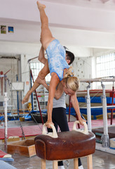 Female gymnast in bodysuit during workout at vaulting buck and man helping