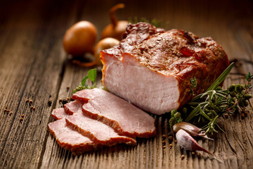 Smoked meats, sliced smoked pork loin on a wooden  table with addition of fresh  herbs and aromatic spices.  Traditional smoked meat smoked in apple  and beech  wood, Natural product from organic farm