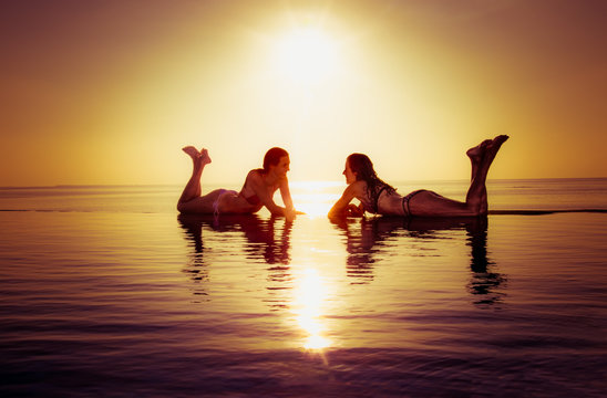 Two beautiful girls enjoy in the infinity pool in sunset.