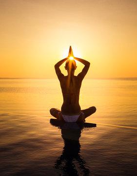 Woman has Yoga at infinity pool during sunset. Maldives