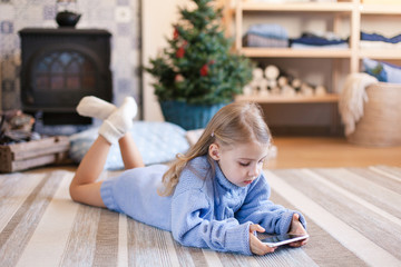 Child is using mobile phone under Christmas tree at home. Kid is playing in children games, looking at devices. Girl in blue knitted sweater with her present or gift is laying on warm floor.