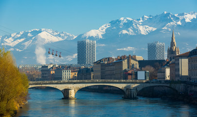 Fotobehang Stad aan het water Grenoble with cable car against backdrop of snowy Alps