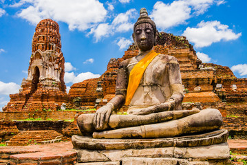 Thailand, Stupa and Buddha sculpture with orange sash in Ayutthaya old Temple
