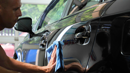 Two specialist dries the car from moisture, car washing. Concept: Drying Machines, Professionals, Auto Service.