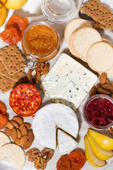 assortment of snacks with cheeses, fruits and nuts, top view vertical