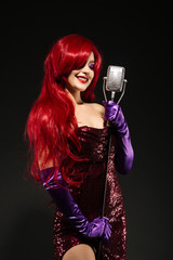 Young smile redhead woman with very long hair in red gown with microphone on the stand on a black background.