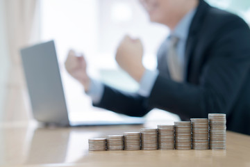 Businessman with coffee cup working at workplace. coins stack