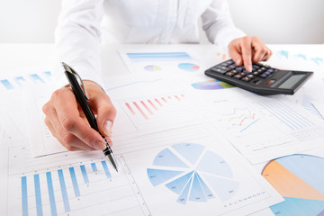 Business woman pointing at graph document close-up.