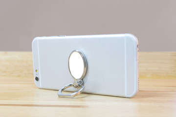 Smartphone holder in ring concept on wood table. Blank mobile accessory for montage or your design.