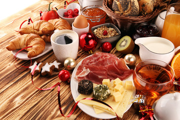 breakfast on table with bread buns, croissants, coffe and juice on christmas day. xmas holiday morning.