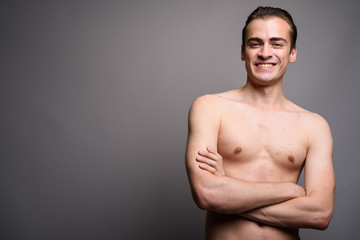 Young handsome man smiling shirtless with arms crossed against gray background