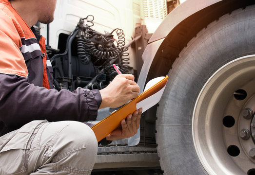Inspection safety a trucks, truck driver holding clipboard with checking a truck tire.