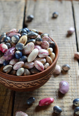Assortment of young legumes and beans of different varieties and colors in a clay bowl. Raw food. Healthy diet concept. Selective focus