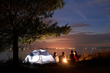 Back view of four tourists, women and man resting on sea shore around bonfire at tent under tree on smooth water surface and blue evening sky with first stars background. Tourism and camping concept.