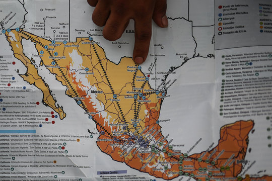 A man points at a map amidst a caravan of thousands of migrants from Central America as they walk to the U.S. from Mexico